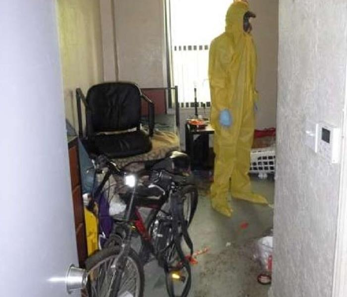 A man in bio-hazard attire standing in a home that needed cleaning