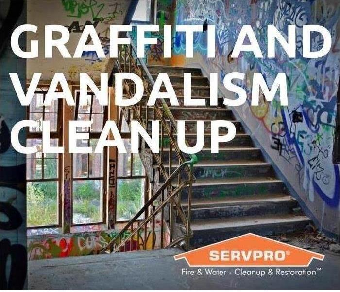 SERVPRO logo on a sign stating that SERVPRO does graffiti and vandalism cleanup. A building with graffiti is the background