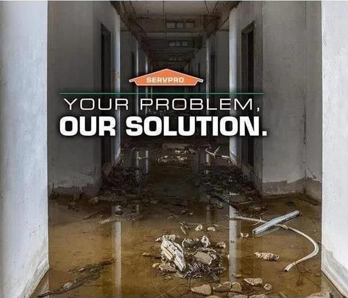 Flooded building with SERVPRO logo and words that say 'Your problem, Our solution'