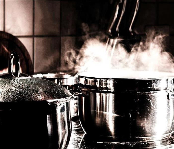 Two pots on the stove that are boiling with steam